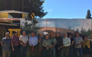 State, federal, non-profit, and individual partners in the I-90 corridor stand in front of a graphic rendition of the wildlife overpass now being constructed on I-90 at the groundbreaking event.