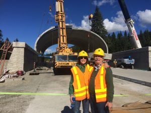 I-90 Wildlife Bridges Coalition staff, Charlie Raines and Jen Watkins, standing in front of the Lake Keechelus Wildlife Overpass as it is constructed.